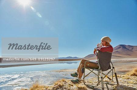 Woman sitting in camping chair, looking at view, Salar de Chalviri, Chalviri, Oruro, Bolivia, South America