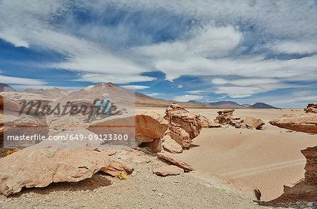 Woman sitting on rock, looking at view, Villa Alota, Potosi, Bolivia, South America