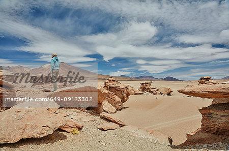 Woman standing on rock, looking at view, Villa Alota, Potosi, Bolivia, South America