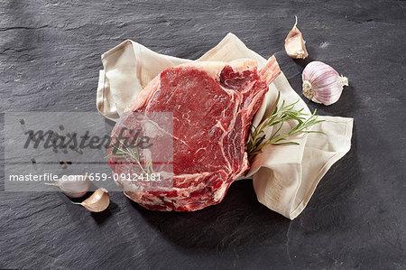 A raw beef rib, garlic, rosemary and peppercorns