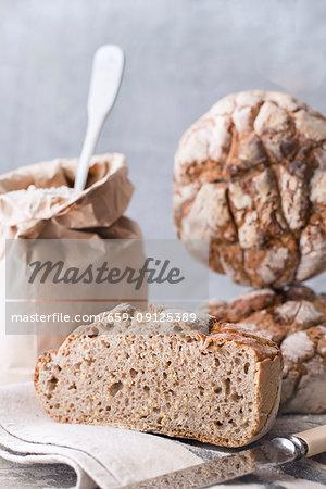 Homemade sourdough bread on a cloth next to a bag of flour and a knife