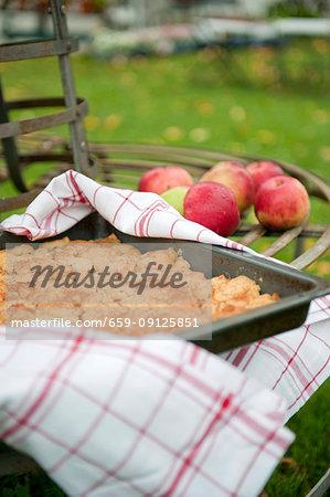 Apple pie in a tin on a garden bench