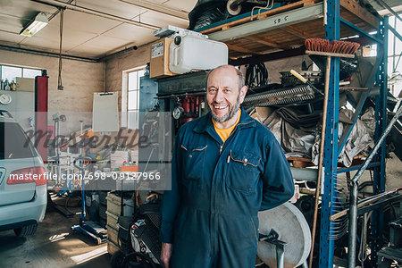 Portrait of smiling male mechanic standing sat car repair shop