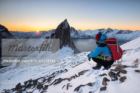 Hikers watch the first sun that it hits the peak called Segla, Hesten, Fjordgard, Mefjorden, Senja, Tromso, Norway, Europe.