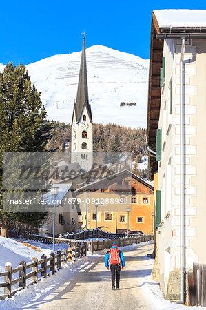 Tourist walk in a street of Zuoz village. Zuoz, Engadine, Graubünden, Switzerland.