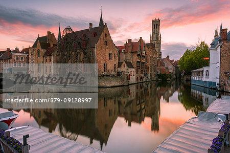 The medieval Belfry and historic buildings reflected in Rozenhoedkaai canal at dusk, Bruges,flemish region, West Flanders, Belgium, Europe