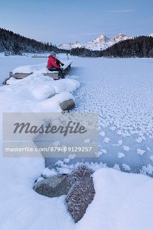 Man sitting on shore of frozen lake, Lej da Staz, St Moritz, canton of Graubünden, Engadine, Switzerland