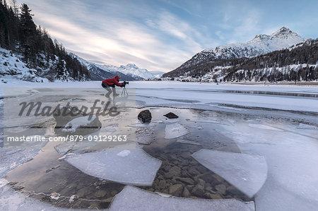 Photographer at dawn on frozen Lake Champfer, Silvaplana, Maloja Region, canton of Graubunden, Engadin, Switzerland