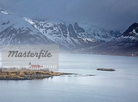 Remote church along fjord waterfront below snowy mountains, Sildpoinesnet, Austvagoya, Norway