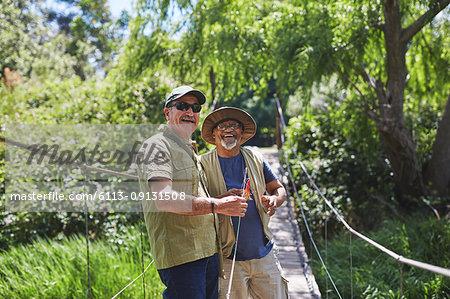 Portrait happy active senior men friends fishing on sunny summer footbridge
