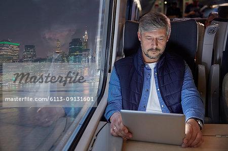 Man using digital tablet on passenger train at night