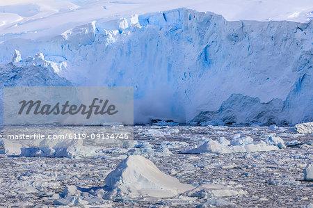 Ice avalanche, glacial calving into iceberg filled Neko Harbour, early morning sun, Graham Land, Antarctic Continent, Antarctica, Polar Regions
