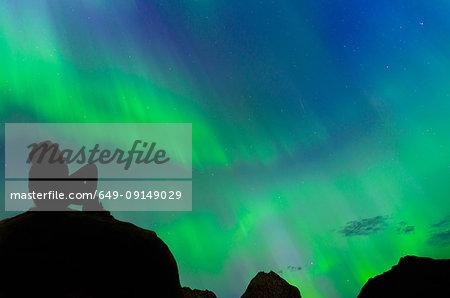 Tourist looking up at Aurora Borealis, Narsaq, Vestgronland, Greenland