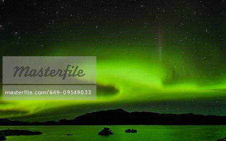 Aurora Borealis above mountain range, Narsaq, Vestgronland, Greenland