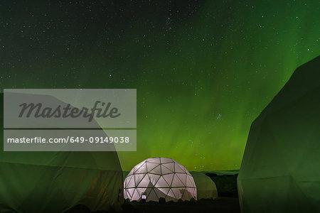 Lit up dome tent, Aurora Borealis in background, Narsaq, Vestgronland, Greenland
