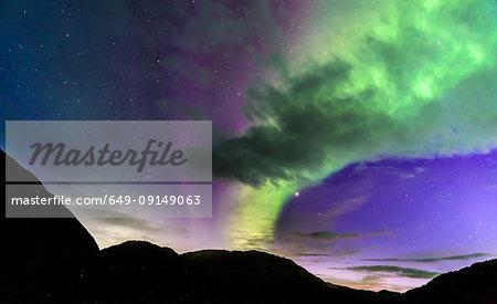 Aurora borealis over silhouette of mountains, Narsaq, Vestgronland, Greenland