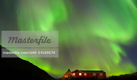 Landscape with log cabin and aurora borealis at night, Narsaq, Vestgronland, South Greenland