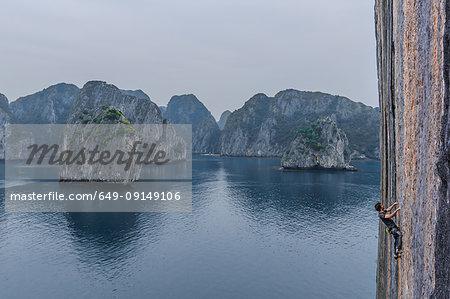 Man rock climbing on limestone rock, Ha Long Bay, Vietnam