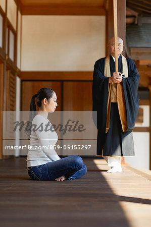 Japanese woman meditating at a temple