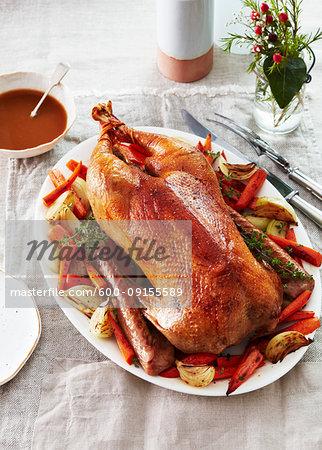Roast goose on a platter with vegetables for a festive dinner