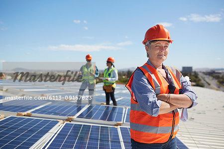 Portrait confident female engineer at sunny solar power plant