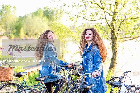 Fashion blogger twins with pushbikes by lake, Mantova, Lombardia, Italy