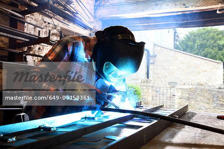 Blacksmith welding metal on workbench in blacksmiths shop