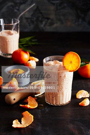 Orange smoothie with orange slices on a dark countertop