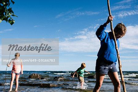 Siblings exploring water with sticks, Kingston, Canada