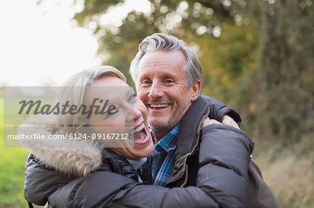 Portrait happy mature couple hugging in park