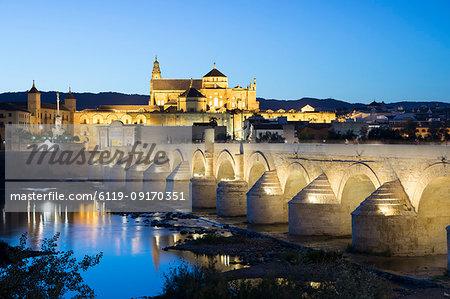 The Mezquita and Roman Bridge over the river Guadalquivir floodlit at night, Cordoba, Andalucia, Spain, Europe