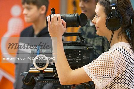 Teenage girl operating video camera, vlogging