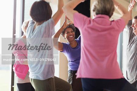 Smiling active senior woman exercising, practicing yoga tree pose
