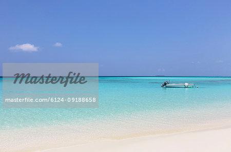 Boat moored in sunny, tranquil ocean, Maldives, Indian Ocean