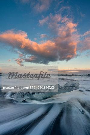 Block of ice on the black beach at sunset in Jokulsarlon Glacier Lagoon, Austurland, Eastern Iceland, Iceland, Europe