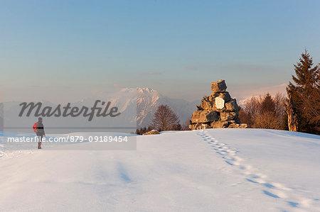 A hiker observes the partisan tombstone on Costa Mount, Prealps of Belluno, Farra d'Alpago, Belluno province, Veneto, Italy