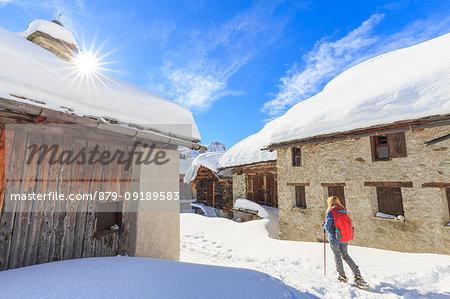 Young girl walk with snowshoes in the village of Grevasalvas, Engadin Valley, Graubünden, Switzerland, Europe.