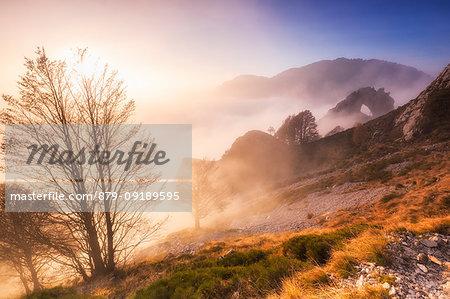 The sun illuminates the fog with the Porta di Prada in the background. Bocchetta di Prada, Grigna Settentrionale(Grignone), Northern Grigna Regional Park, Lombardy, Italy, Europe.
