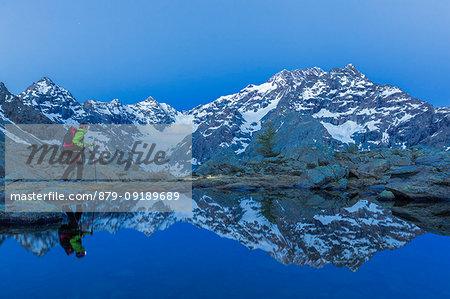 A hiker walks at dusk near a lake that mirrored the mountain range of Mount Disgrazia. Chiareggio valley, Valmalenco, Valtellina, Lombardy, Italy, Europe.