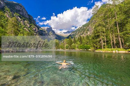 A girl swims in a clear alpine lake. Val di Mello(Mello Valley), Valmasino, Valtellina, Lombardy, Italy, Europe.