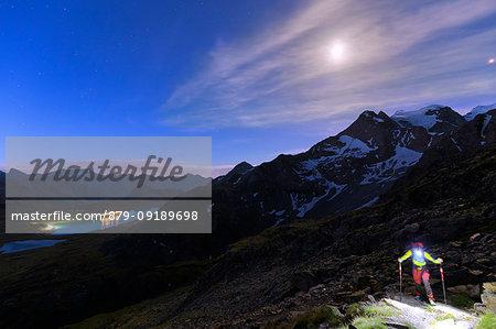 Hiker walks in the night of full moon with view on Bernina Pass, Engadin, Graubünden, Switzerland, Europe.