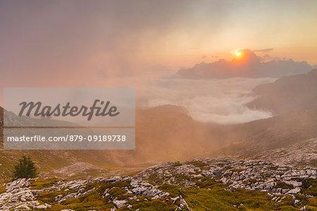 The sun rises in Cortina d'Ampezzo hidden by the morning fog, Belluno district, Veneto, Italy