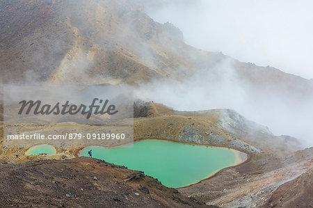 Hiker descending towards Emerald Lakes. Tongariro Alpine Crossing, Tongariro NP, Waikato region, North Island, New Zealand.