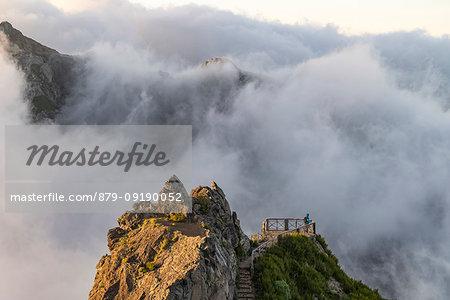 Hiker admiring the view from Ninho da Manta lookout. Pico do Arieiro, Funchal, Madeira region, Portugal.