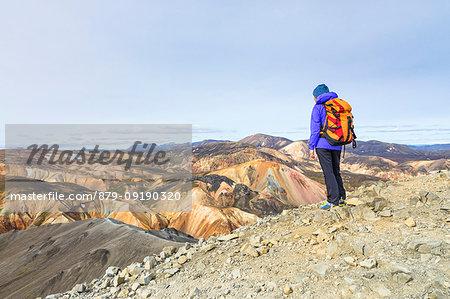 A trekker is looking at the Landmannalaugar panorama from the top of Blahnukur mountain (Landmannalaugar, Fjallabak Nature Reserve, Highlands, Southern Region, Iceland, Europe) (MR)