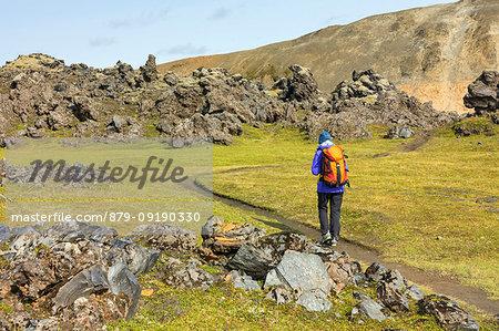 Graenagil footpath: a trekker is walking through the Laugahraun lava field in Landmannalaugar (Fjallabak Nature Reserve, Highlands, Southern Region, Iceland, Europe) (MR)