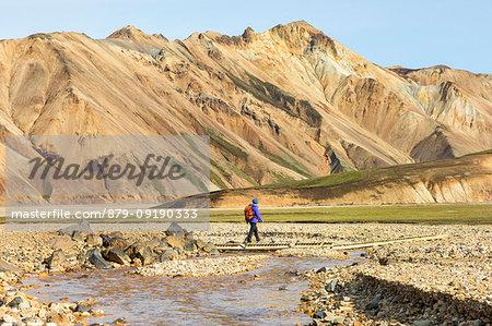 A trekker is walking to the Blahnukur mountain in Landmannalaugar (Fjallabak Nature Reserve, Highlands, Southern Region, Iceland, Europe) (MR)