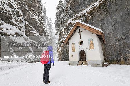 A girl is looking the small Church inside the Sottoguda Serrai Gorge at the foot of Marmolada (Sottoguda, Rocca Pietore, Belluno province, Veneto, Italy, Europe) (MR)