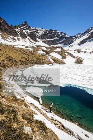 Photographer at Laj dal Teo where snow begins to melt due to spring thaw Poschiavo Valley Canton of Graubunden Switzerland