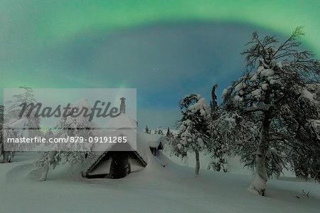 Northern lights on wood hut covered with snow, Pallas-Yllastunturi National Park, Muonio, Lapland, Finland